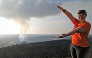 UF Online image of Lauren Huffman Kahre doing the Gator chomp next to a volcano